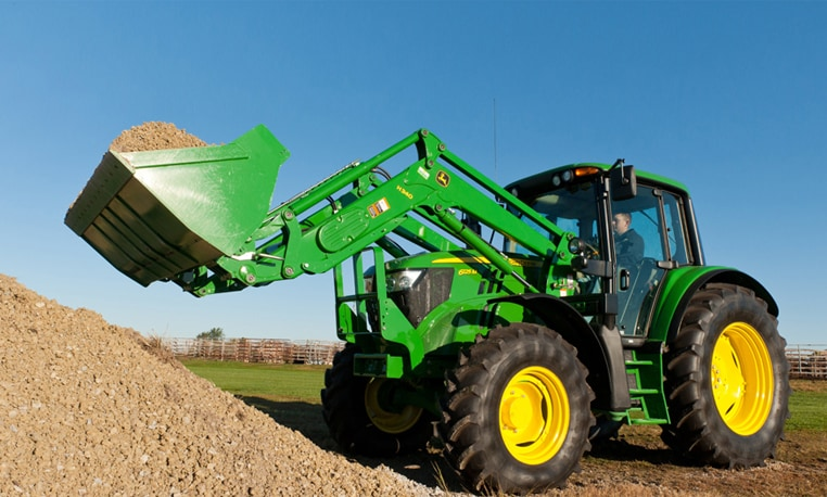 John Deere tractor with loader attachment lifting a bucket full of dirt