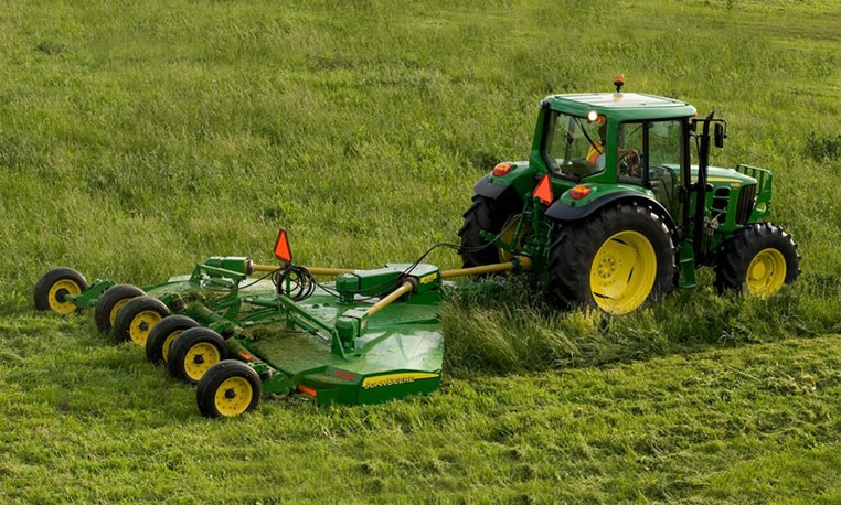 John Deere tractor with mowing attachment working in a field