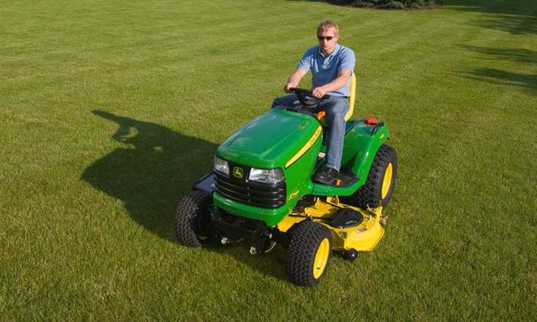 Man using a John Deere Riding Mower to cut grass