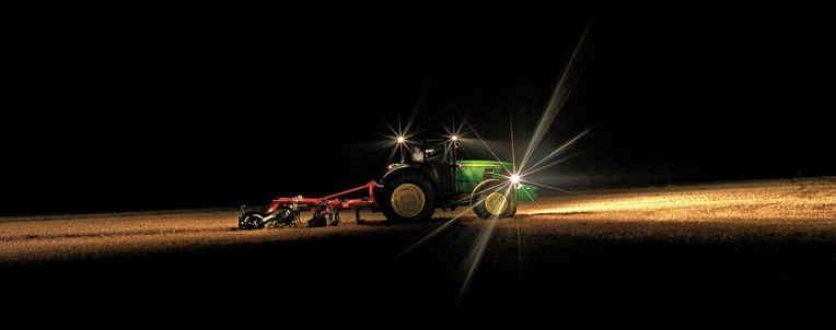 Tractor tills field at night