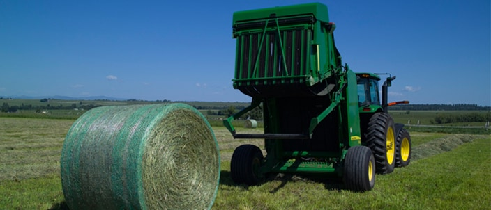 Image of round baler with round bale in field.