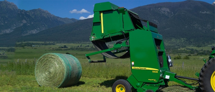 Image of 568 round baler in field ejecting a round bale.