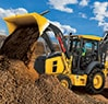 Left side view of the 310L EP Backhoe Loader with loader raised and dumping gravel