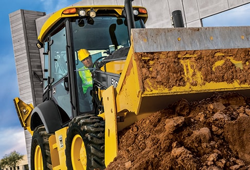 310SL Backhoe Loader with a multi-purpose bucket unloading dirt using the clamshell function of the bucket