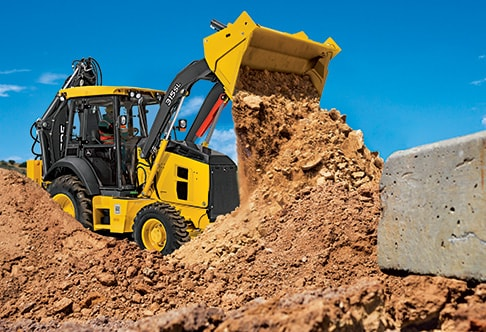 Right side view of the 315SL Backhoe Loader with bucket raised and dumping dirt into a pile