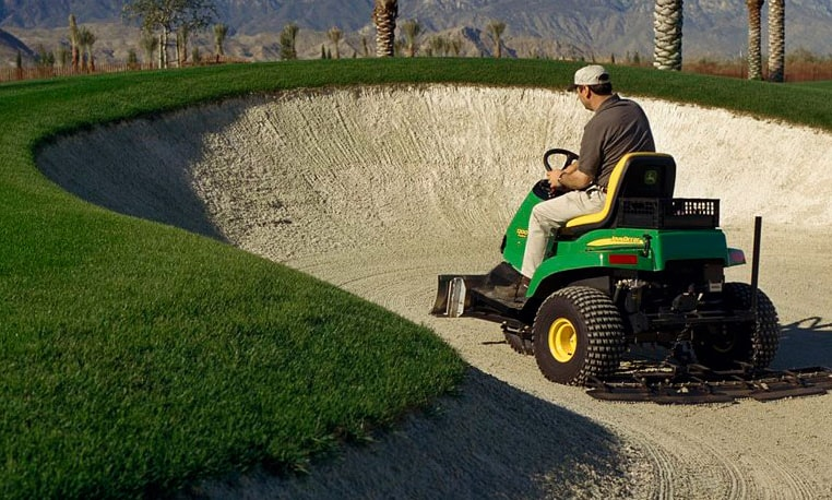 Groundskeeper using a John Deere bunker rake on a golf course