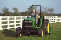 Man using a John Deere Tractor with attached 25A Flail Mower to cut grass next to a white fence