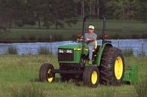 Man using a John Deere Tractor with attached 370 Flail Mower to cut grass near a pond