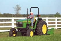 Man using a John Deere Tractor with attached 390 Offset Flail Mower to cut grass near a white fence