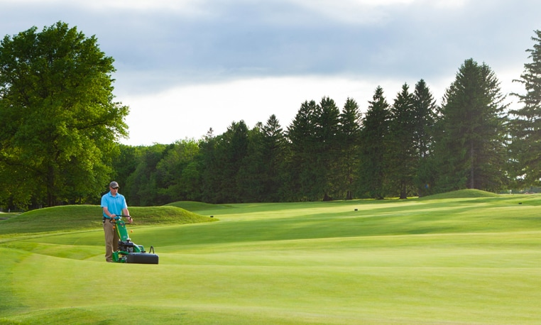 Man mows golf course fairway with E-Cut Hybrid Mowers