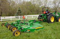 HX15 Flex-Wing Rotary Cutter mowing grass near a white fence