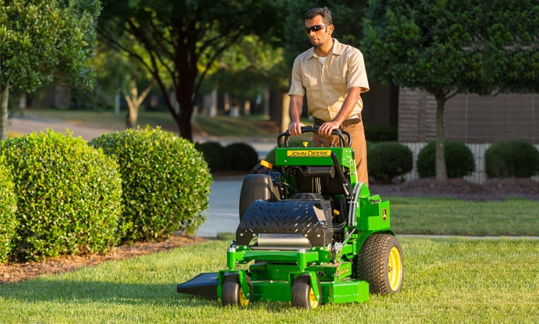 Man operates a QuikTrak 600 M Series Mower in a residential area