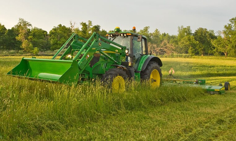 John Deere tractor with mowing attachment in a field
