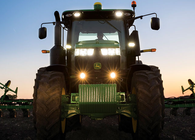 A head on shot of the 7250R Tractor with lights on at dusk