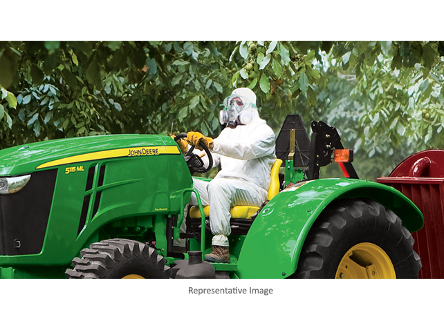 Man with protective mask uses 5100ML Low-Profile Utility Tractor to spray trees