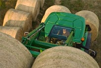 Overhead view of a 6R Series Tractor with loader attachment lifting two hay bales