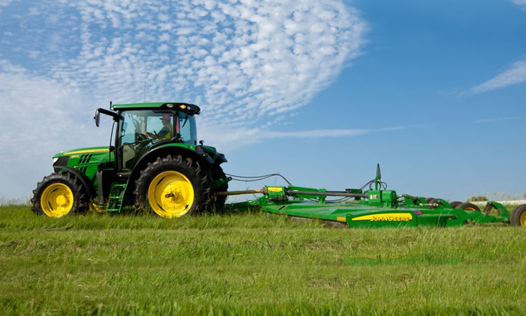 6R Series Tractor mowing a large field