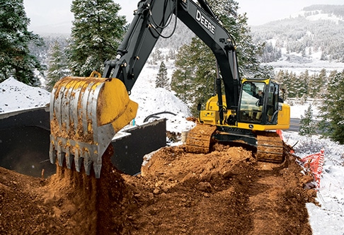 250G LC excavator removing dirt from around a home foundation in the mountains