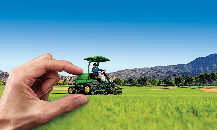 Image of a hand controlling a fairway mower