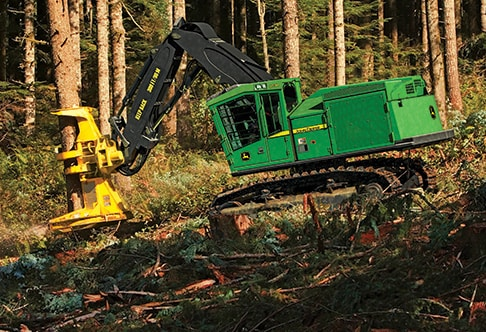Left hand side view of the 903M Tracked Feller Buncher cutting a tree
