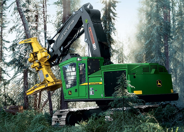 Side view of a 953M Tracked Feller Buncher sawing into a tree in the forest