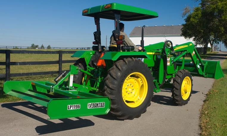 A Land Plane is shown attached to the back of a John Deere tractor