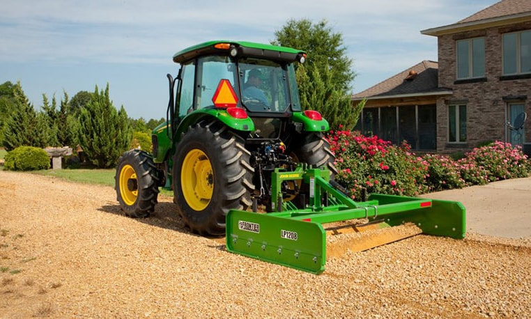 John Deere tractor uses a land plane in front of a residence
