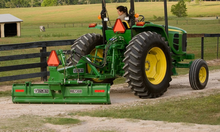 Woman operates a John Deere tractor with a rear blade