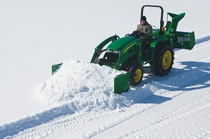 Man using a John Deere tractor with AS10H Snow Push to clear snow