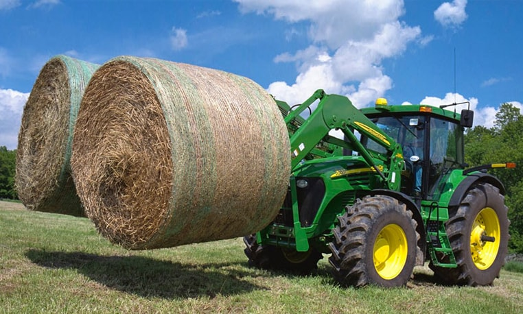 Operator uses Bale Spears to haul 2 large round bales