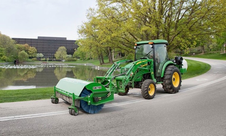 A Deere tractor sweeps the entry road to John Deere World Headquarters