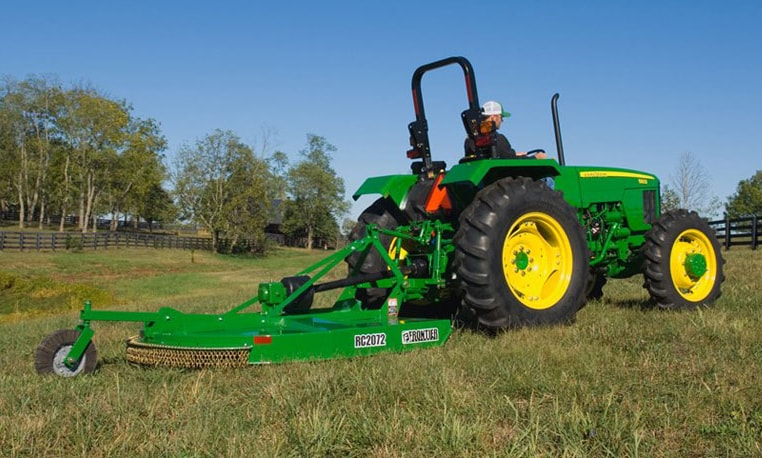 A John Deere tractor pulls a rotary mower