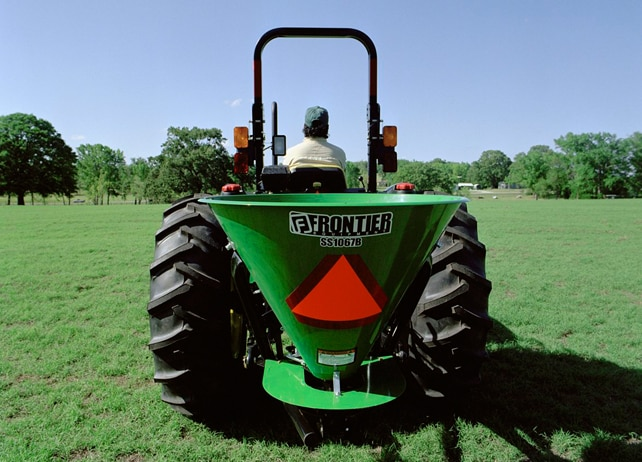 Rear view of a John Deere tractor with SS10B Series Broadcast Spreader in a grassy field dotted with trees