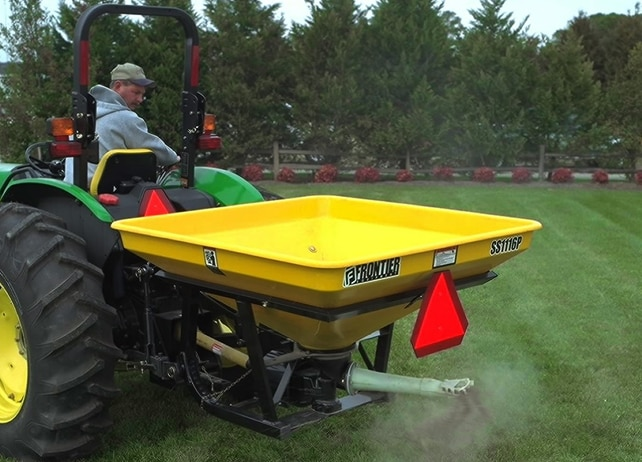 Man driving a John Deere tractor and looking back at an attached SS11P Series Pendular Spreader