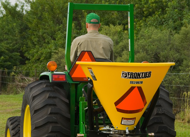 Rear view of a man driving a John Deere tractor with SS20B Series Broadcast Spreader with trees in the background
