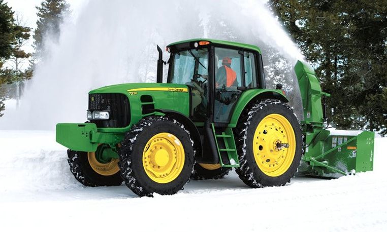 Man uses WorkSite Pro Attachment on a John Deere 7330 to move snow