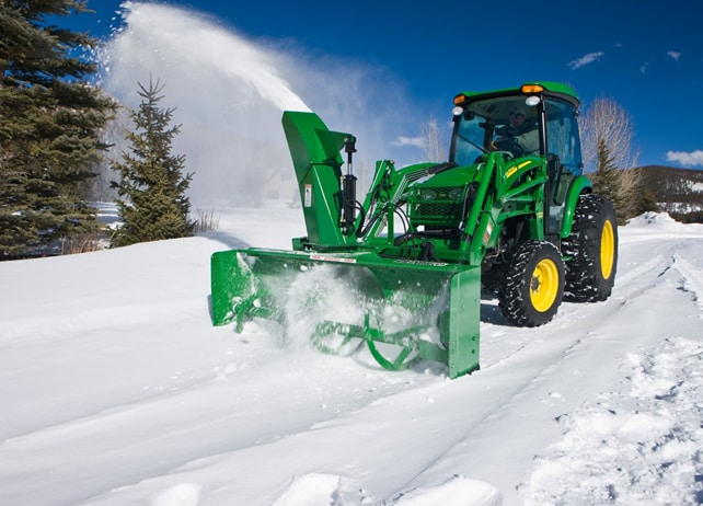 John Deere tractor using a SB21 Loader-Mount Snow Blower to clear snow