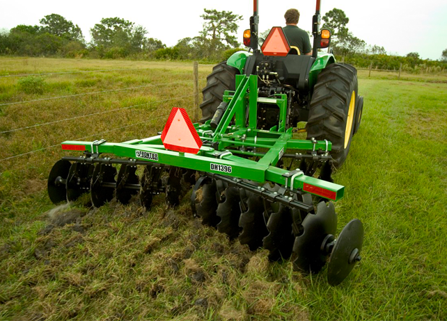 Rear view of a John Deere tractor with DH12 Series Disk Harrows at work in a field