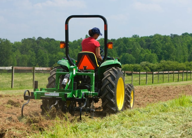 Rear view of a woman driving a John Deere tractor with MF22 Series Mulch Finisher