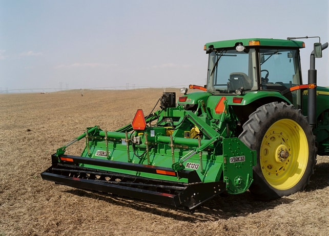 Rear view of a John Deere tractor using a RC13 Row-Crop Rotary Tiller to plow a field