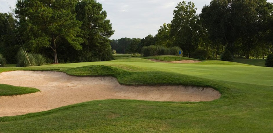 Golf course green surrounded by bunkers and trees