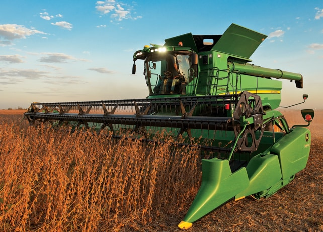 S670 Combine with lights on harvesting a soybean field at dusk