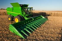 S690 Combine with corn head attachment sitting in a partially harvested cornfield
