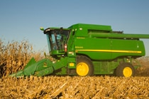Side view of a John Deere Combine with 608C StalkMaster™ Corn Head working in a field