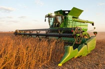 635FD HydraFlex™ Draper on a John Deere Combine harvesting soybeans at dusk