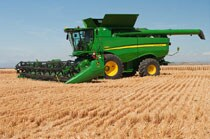 Side view of a John Deere Combine with 640D Draper working in a field