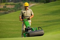 Worker uses walk behind mower on a golf course fairway
