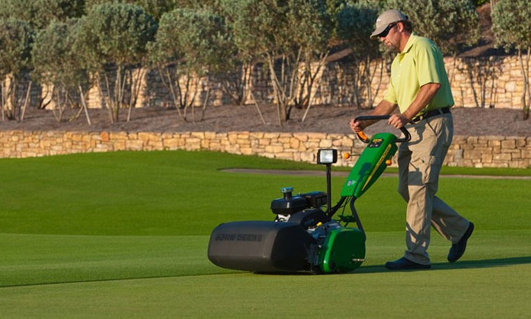 Worker mows golf course green with SL PrecisionCut Walk Greens Mower