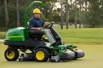 Worker using a 2500B Diesel mower on a green at a golf course