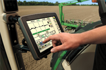 Farmer uses GreenStar 3 2630 Display in tractor cab in a tilled field